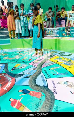 Indian girls playing Snakes and Ladders, Indian Moksha Patamu, an education game against child labour, Kutties Rajiyam - Stock Photo