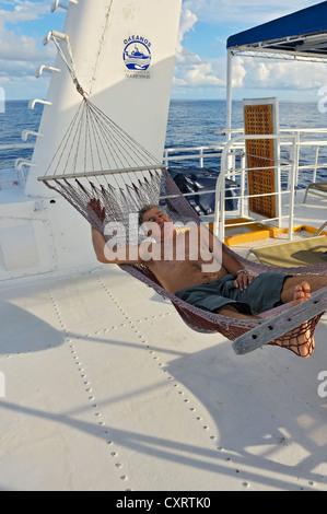 Elderly man, tourist lying in a hammock on the Okeanoss Aggressor, Cocos Island, Costa Rica, Central America - Stock Photo