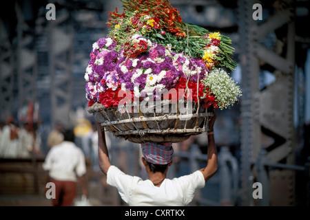 Man carrying flower on his head, near the Flower Market, Howrah Bridge over the Hooghly river, Calcutta, Kolkata, - Stock Photo