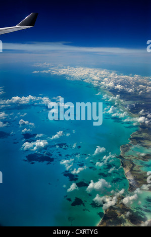 View from an aircraft, clouds, ocean and the wing of an airplane, Cuba, Caribbean - Stock Photo