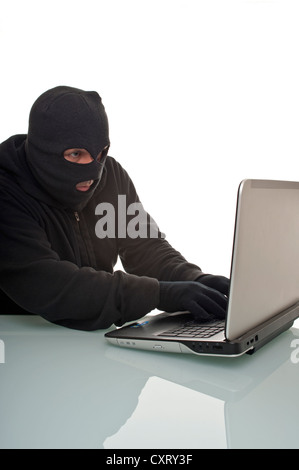 Hacker surfing the internet with a laptop computer, symbolic image for computer hacking, computer or cyber crime, - Stock Photo