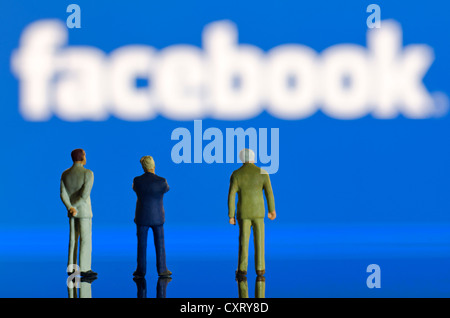 Businessmen, miniature figures standing in front of a blurred Facebook logo, symbolic image - Stock Photo