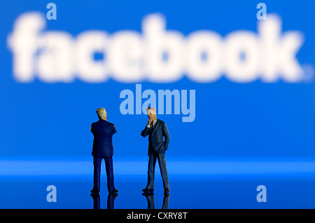Two businessmen, miniature figures standing in front of a blurred Facebook logo, symbolic image - Stock Photo