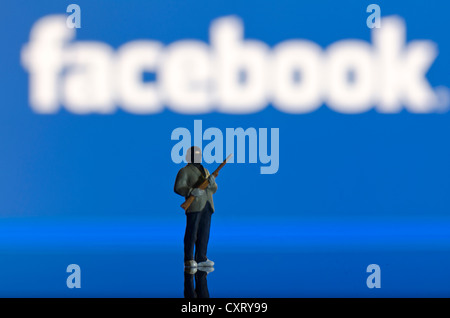 Islamist carrying a weapon, miniature figure standing in front of a blurred Facebook logo, symbolic image - Stock Photo