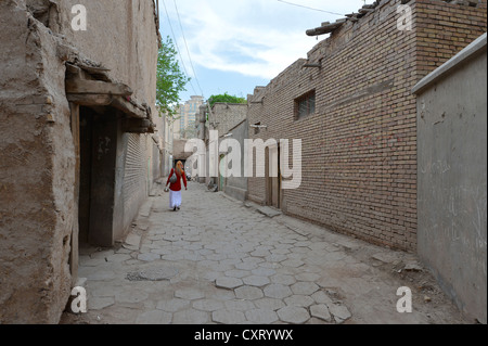 Muslim woman walking though an alleyway in the old town of the Uyghur quarter, old adobe brick architecture, Silk - Stock Photo