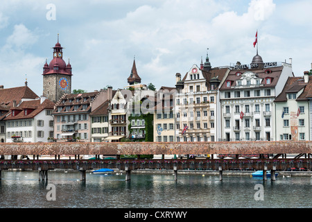 View of Kapellbruecke bridge as seen across the Reuss river, Hotel Des Alpes at the back, tower of the town hall - Stock Photo