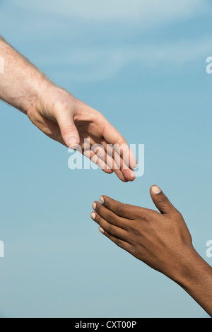 Western and Eastern hand shake against a blue sky - Stock Photo