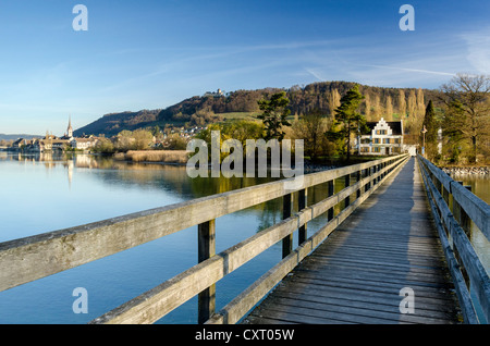 Wooden bridge across the Rhine river leading to Werd island, the historic district of Stein am Rhein on the left, - Stock Photo