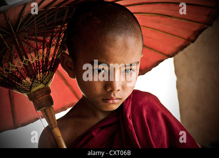 Buddhist novice holding an umbrella, Bagan, Burma, Myanmar, Southeast Asia, Asia - Stock Photo