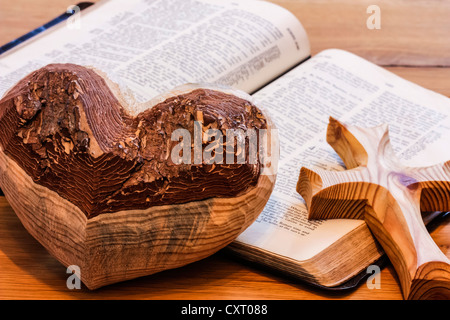 Wooden heart and a wooden cross lying on a bible