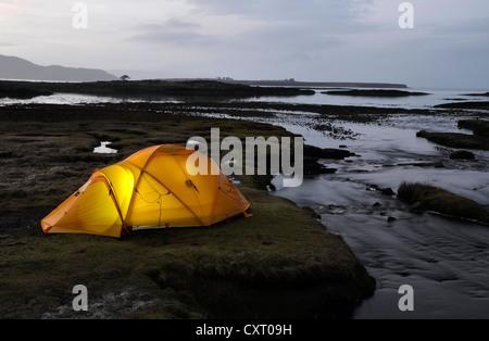 Yellow illuminated expedition tent, trekking tent, on a river estuary, at dusk, Isle of Skye, Scotlan, United Kingdom, - Stock Photo