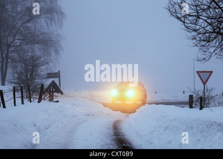 Car in a winter landscape covered in snow, fog, dusk, Bergneustadt, North Rhine-Westphalia, Germany, Europe - Stock Photo