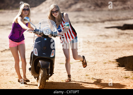 Two young women pushing a motor scooter on the beach - Stock Photo