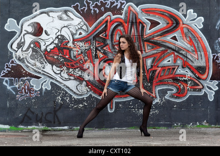Young woman in a white top, denim hot pants, black stockings and high heels posing in front of a graffiti wall - Stock Photo