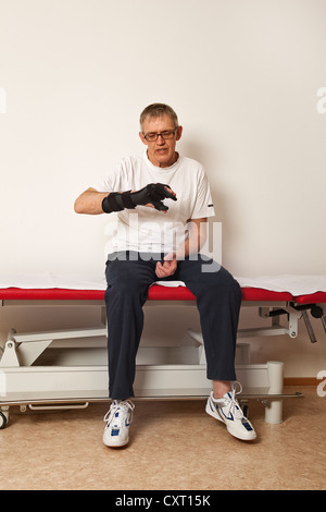 Man wearing a hand orthosis - Stock Photo