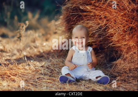 in a field near a haystack funny kid in blue suit - Stock Photo