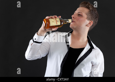 Young man holding a bottle of whiskey - Stock Photo