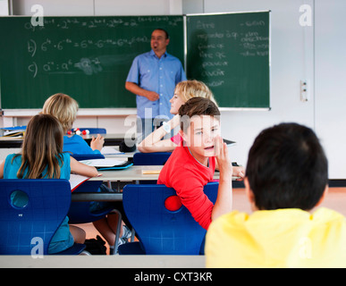 Schoolboy turning around to his classmates during the class - Stock Photo