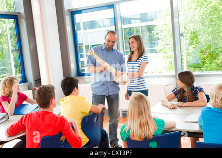 Schoolgirl standing beside a teacher holding a model of the spine in a classroom - Stock Photo