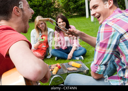 Group of young people at a barbecue in the garden - Stock Photo