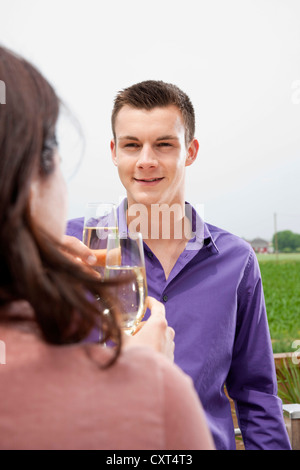 Young man chinking champagne glasses with a young woman - Stock Photo