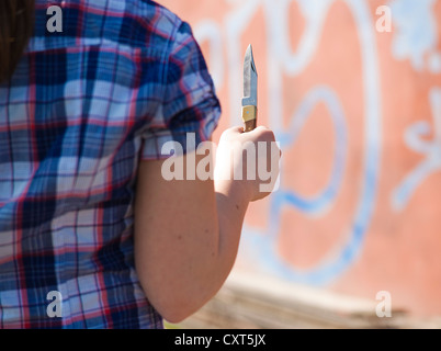 Girl with a knife standing in front of a graffiti-covered wall - Stock Photo