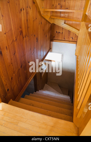 Staircase leading to the basement inside a reconstructed cottage-style residential log home, 1982, Quebec, Canada. - Stock Photo