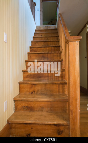 Wooden staircase in the dining room leading to the upstairs floor in an old Canadiana cottage-style residential - Stock Photo