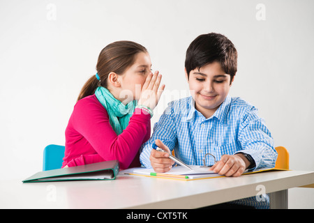 Girl whispering into a boy's ear - Stock Photo