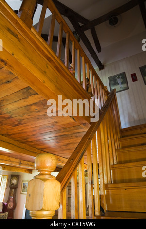 Pinewood staircase leading to the upstairs floor in an old reconstructed Canadiana cottage-style residential log - Stock Photo
