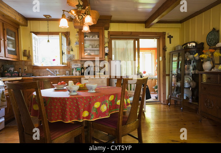 Dining table, chairs and furnishings in the kitchen of an old Canadiana cottage-style wooden siding residential - Stock Photo