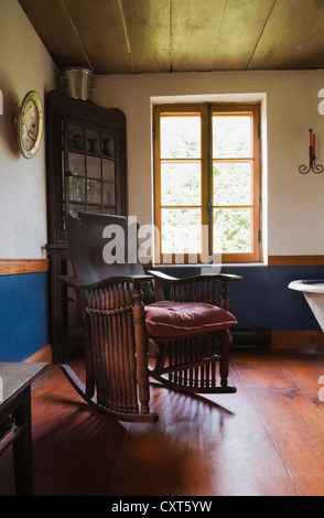 Antique rocking chair and furnishings in the dining room of an old Canadiana cottage-style residential log home, - Stock Photo