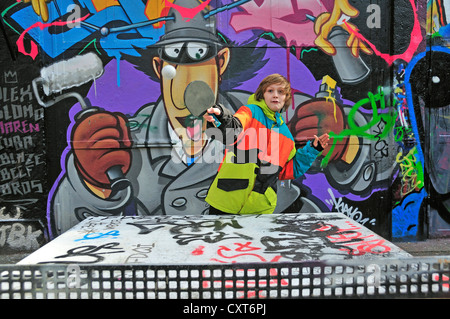 A twelve-year-old boy playing table tennis in front of a graffiti wall, a sports ground in Cologne, North Rhine - Stock Photo