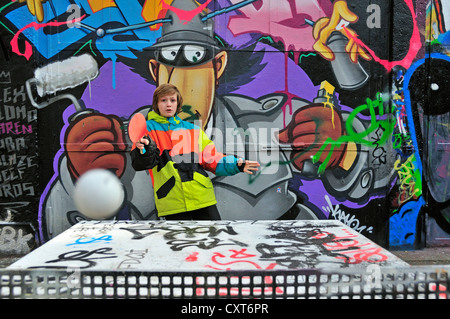 Twelve-year-old boy playing table tennis in front of a graffiti wall, a sports ground in Cologne, North Rhine-Westphalia - Stock Photo