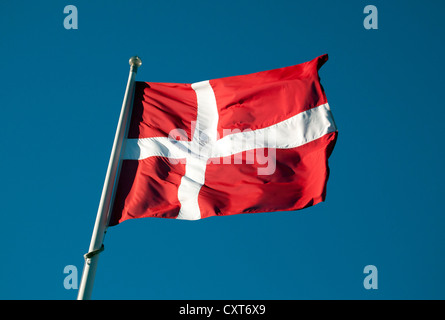 Danish flag flying against a dark blue sky - Stock Photo