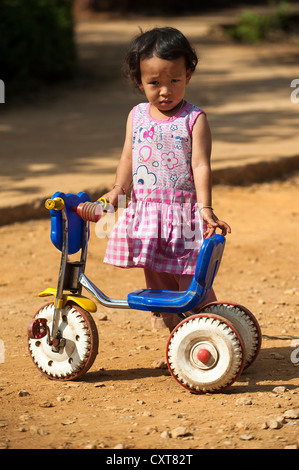 Girl from the Black Hmong hill tribe, ethnic minority from East Asia, with tricycle, Northern Thailand, Thailand, - Stock Photo