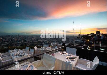 View across the city, Vertigo Bar and Restaurant, roof terrace of the Banyan Tree Hotel, at dusk, Bangkok, Thailand, - Stock Photo