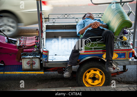 Tuk-tuk driver sleeping in his vehicle, Bangkok, Thailand, Asia - Stock Photo