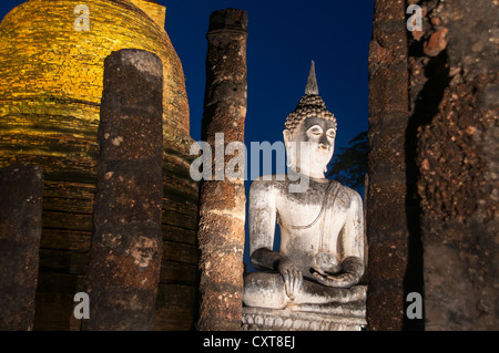 Seated Buddha statue in Wat Sa Si or Sra Sri temple, at night, Sukhothai Historical Park, UNESCO World Heritage - Stock Photo