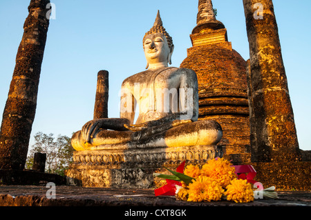 Flowers in front of the seated Buddha statue in Wat Sa Si or Sra Sri temple, Sukhothai Historical Park - Stock Photo