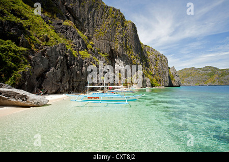 Outrigger boat off the steep limestone coast of Tapiutan Island, Bacuit archipelago, El Nido, Palawan, Philippines, - Stock Photo