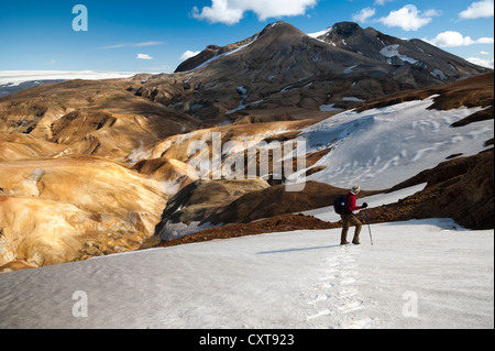 Hiker crossing the snowfield on a trail, snow-capped Rhyolite Mountains, Hveradallir high temperature area, Kerlingarfjoell - Stock Photo