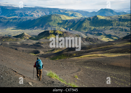View towards Mýrdalsjoekull Glacier, hiker in the Black Lava Desert, with moss-covered mountains along the Laugavegur - Stock Photo