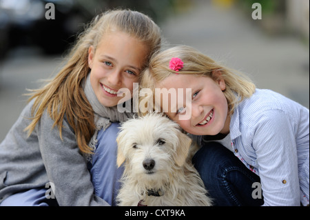 Two girls with a mixed breed puppy - Stock Photo