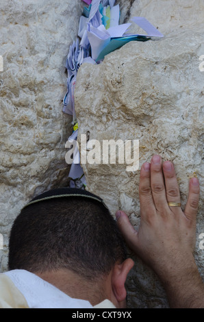 Portrait of a Jew praying at the Western Wall with paper notes in crack. Jerusalem Old City. Israel. - Stock Photo