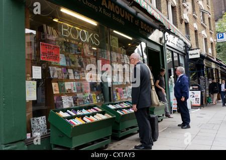 People browsing in the windows of 'Any Amount of Books' in the Charing Cross Road in Central London. - Stock Photo