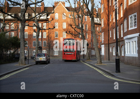 Typical street in London. A red double decker bus can be seen in the background. There are no people in the street. - Stock Photo
