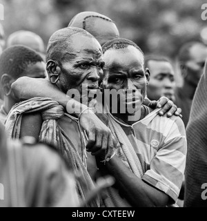 Suri Tribe Men Holding Eachother At A Ceremony Organized By The Government, Kibish, Omo Valley, Ethiopia - Stock Photo