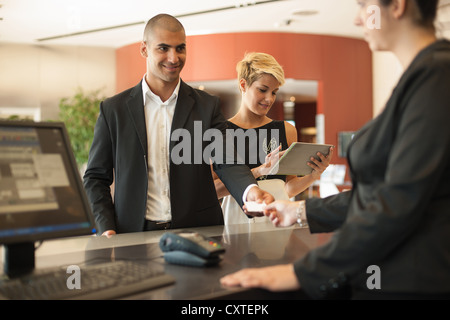 Businessman checking into hotel - Stock Photo