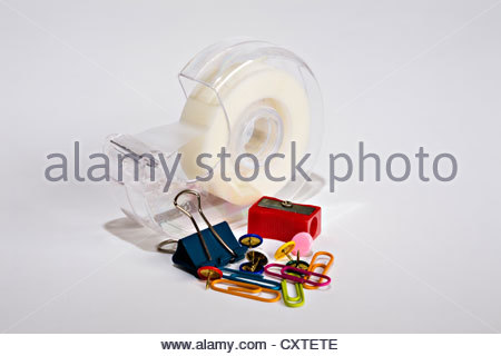 Roll of sellotape tape, coloured paper clips and drawing pins, red pencil sharpener and bulldog clip - Stock Photo
